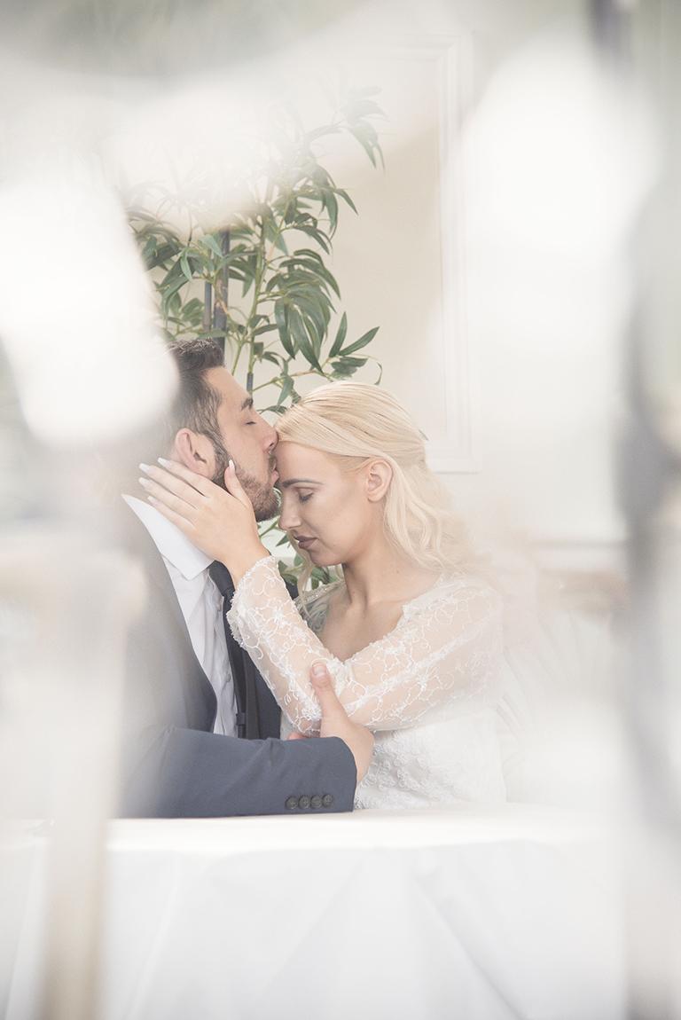 Romantic moment - groom kissing bride on the head