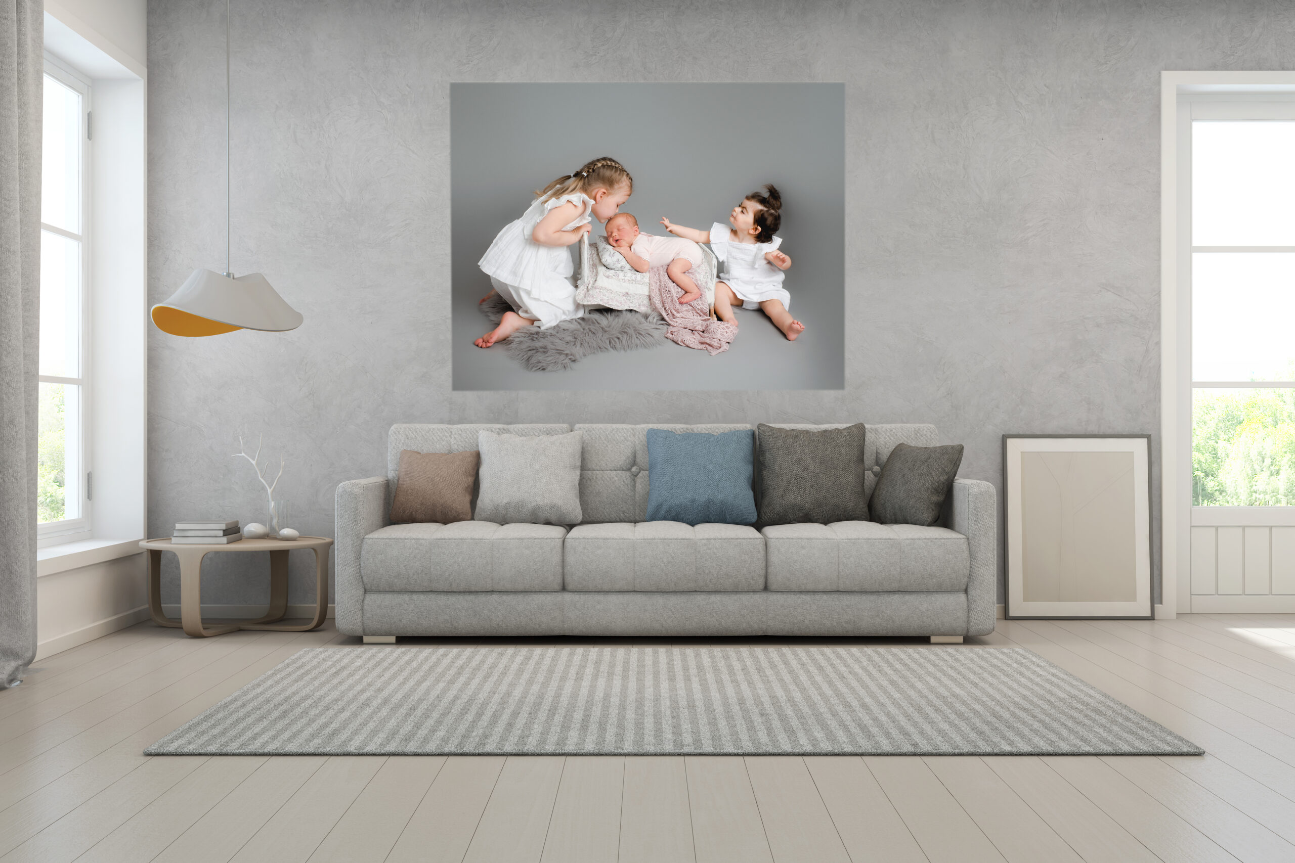 Three beautiful sisters on a photo shot at rachael phillips photography in mansfield nottingham, the newborn baby is in a bed and her sisters are looking at her, it has a grey background