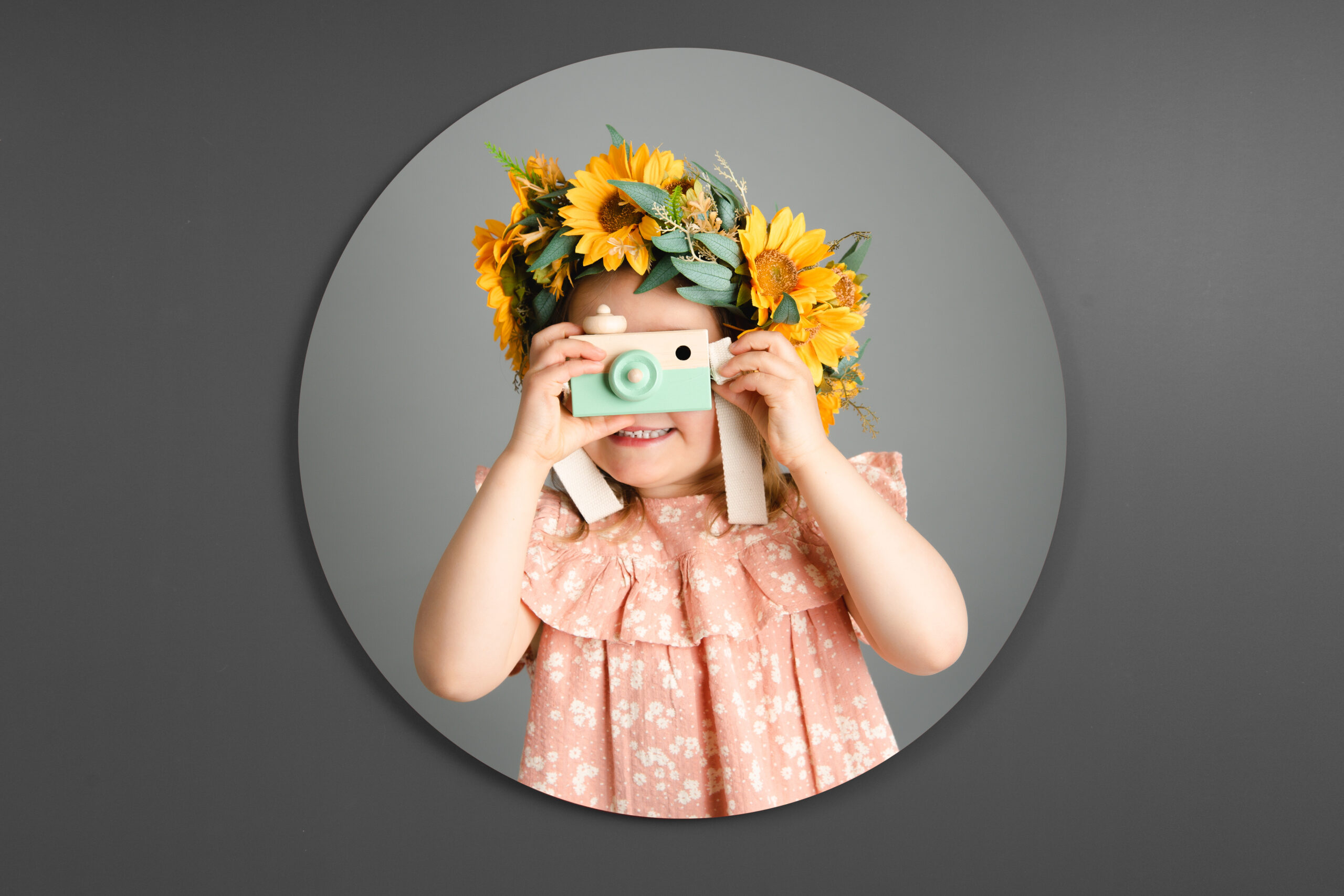little girl on a grey background with sun flowers in her hair and a toy camera