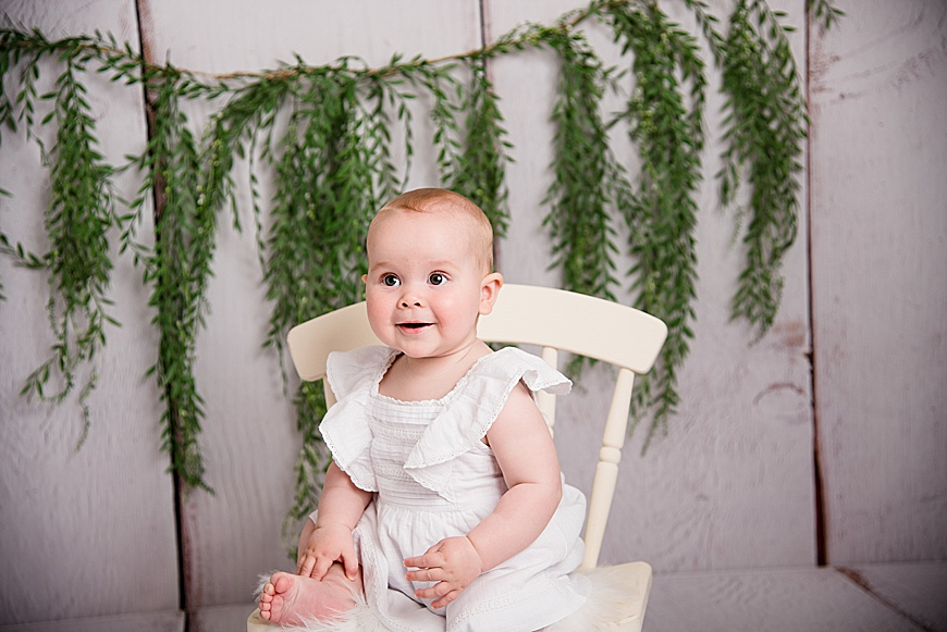 sitters session, little girl smiling and sat on a chair