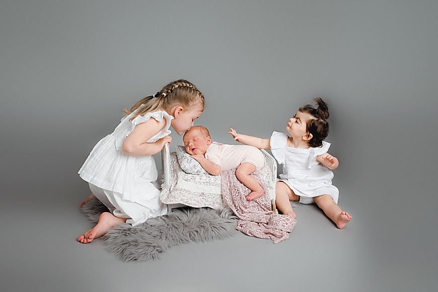 THREE SISTERS IN ONE PHOTO,NEWBORN IS FAST ASLEEP IN A BED AT RACHAEL PHILLIPS PHOTOGRAPHY IN MANSFIELD