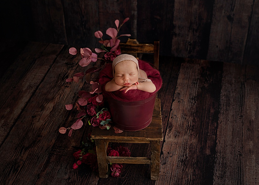 Digital composite photo of a newborn in a bucket on a chair with flowers at rachael phillips photography in mansfield, nottingham