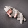 newborn baby boy with an all in our suit on and matching hat - laying on his side alseep at rachael phillips photography studio in mansfield
