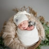 newborn baby boy wrapped in a bucket with a cream hat on and holding an elephant
