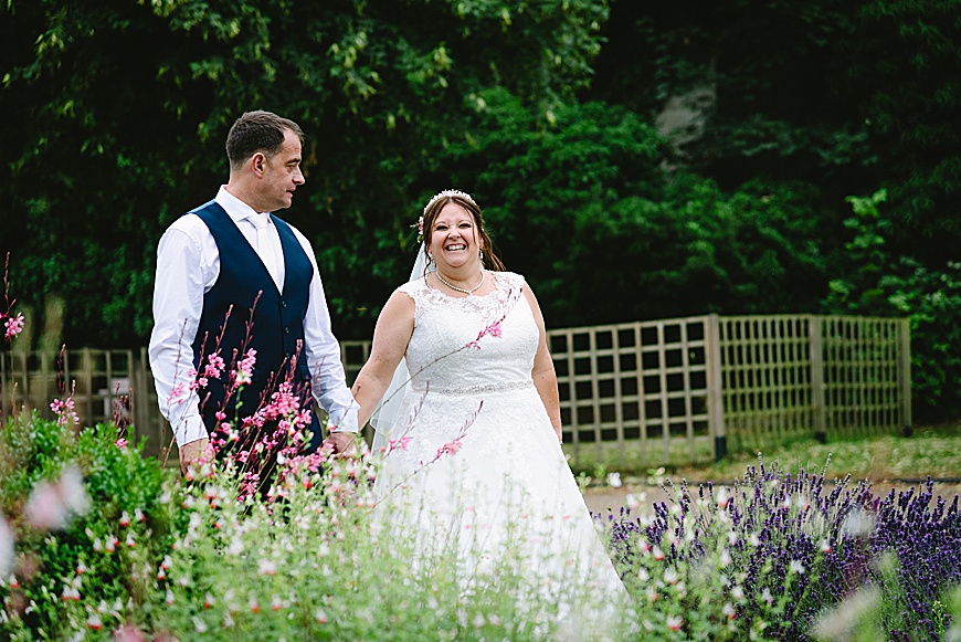 BRIDE AND GROOM AT COLWICK HALL HOTEL WALKING BETWEEN THE FLOWERS