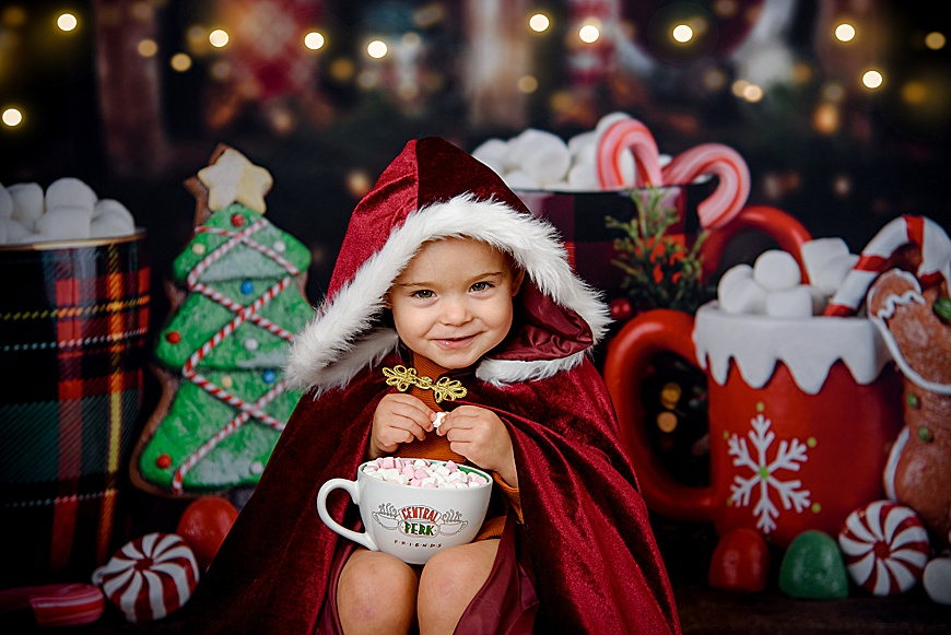 little girl sat with a cup of hot choc and marshmallows