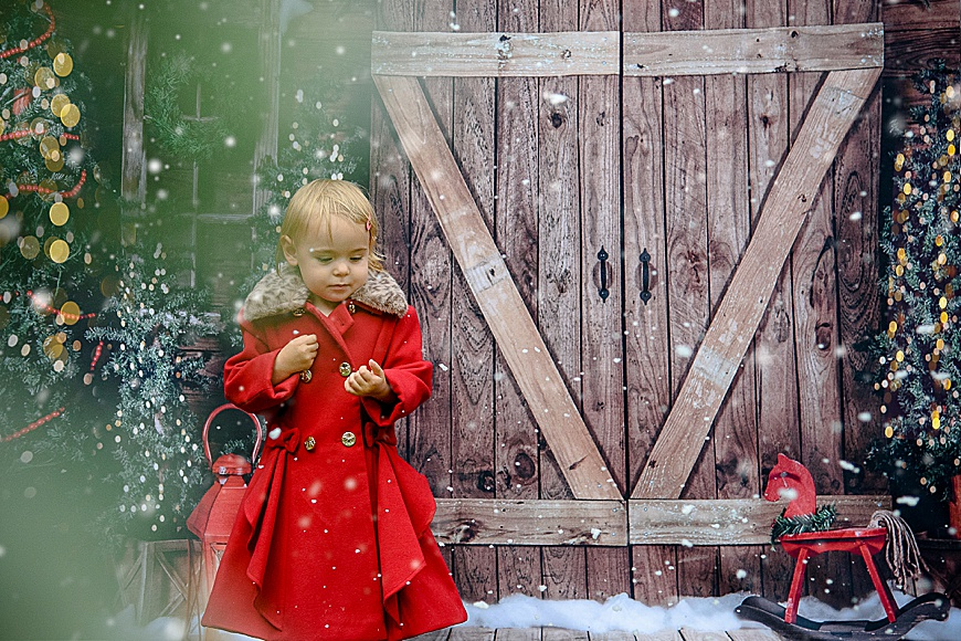 cute little girl in a long red coat outside in the snow on a Christmas backdrop
