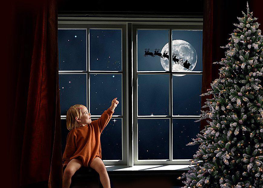 digital backdrop of a christmas window, little girl sees santa fly